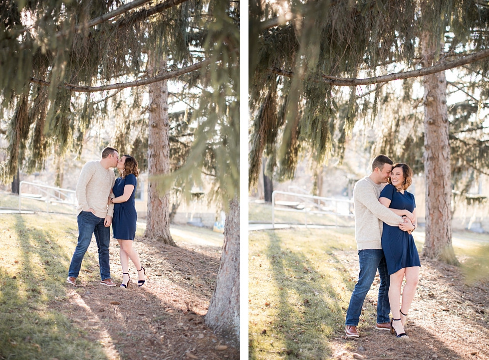 blissful couple with man wrapping his arms around fiance in blue dress kissing her cheek among evergreen trees