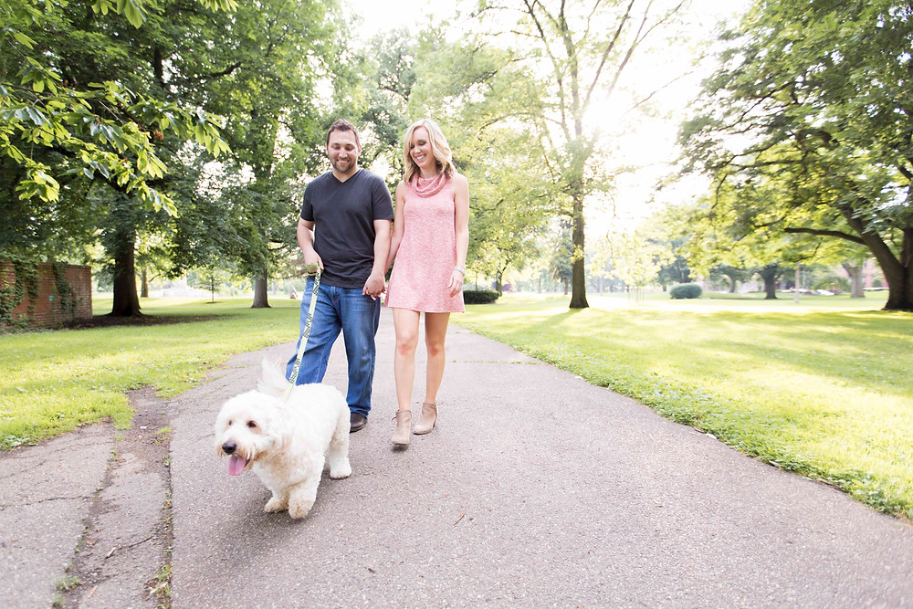 Couple walking their cute dog and holding hands in the NorthSide of Pittsburgh at Allegheny Commons Park West during their Engagement Shoot