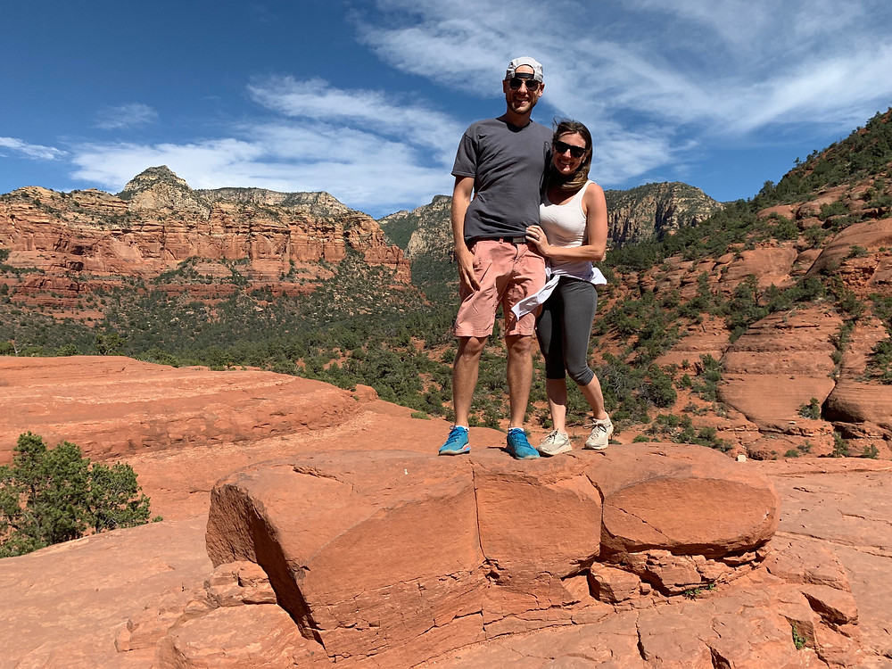 young husband and wife climbing on red rocks on pink jeep tour in sedona arizona
