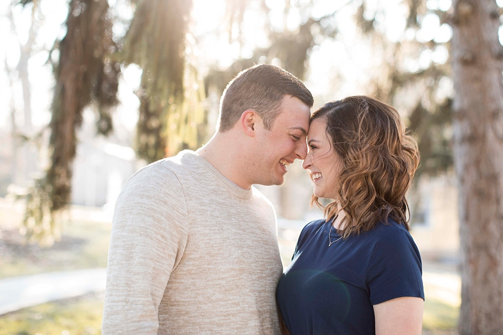 couple smiling with heads together near evergreen trees as the sun sets