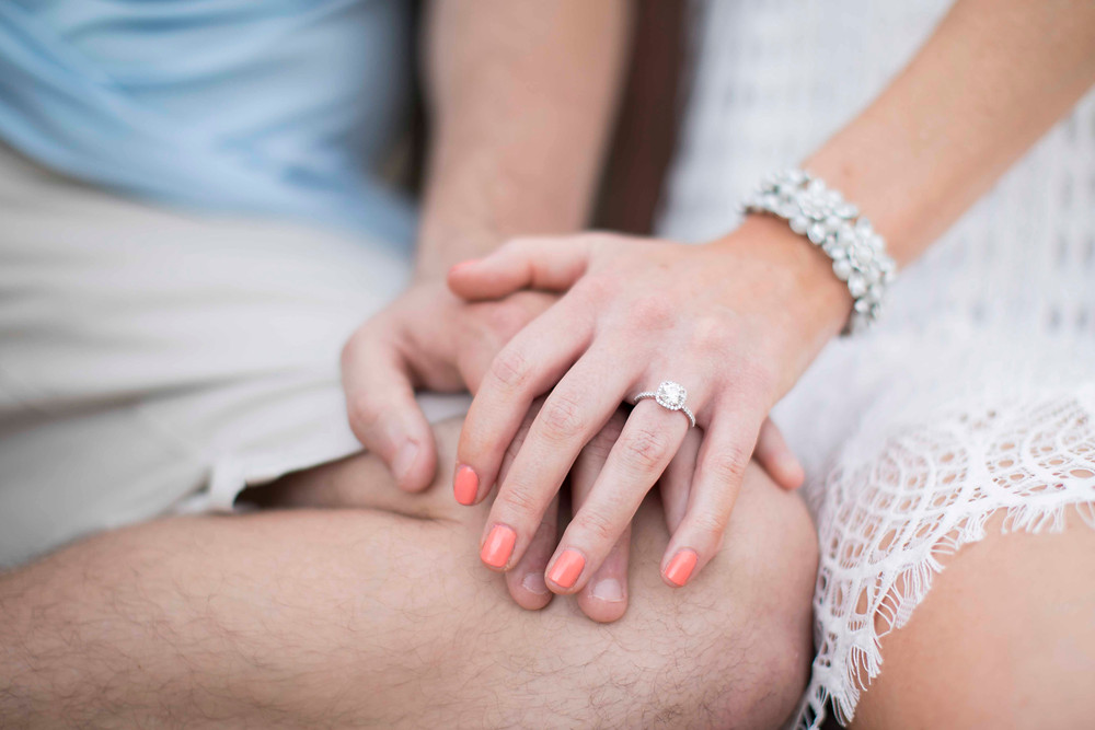 Couple holding hands with focus on bride to be's beautiful ring