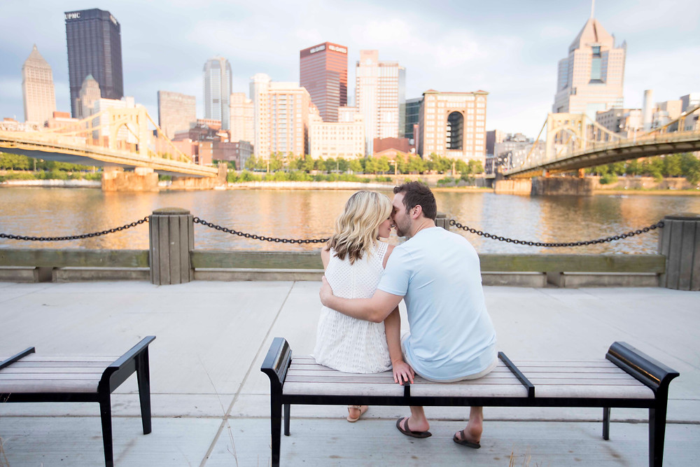 Couple kissing on park bench with Pittsburgh Skyline as the backdrop