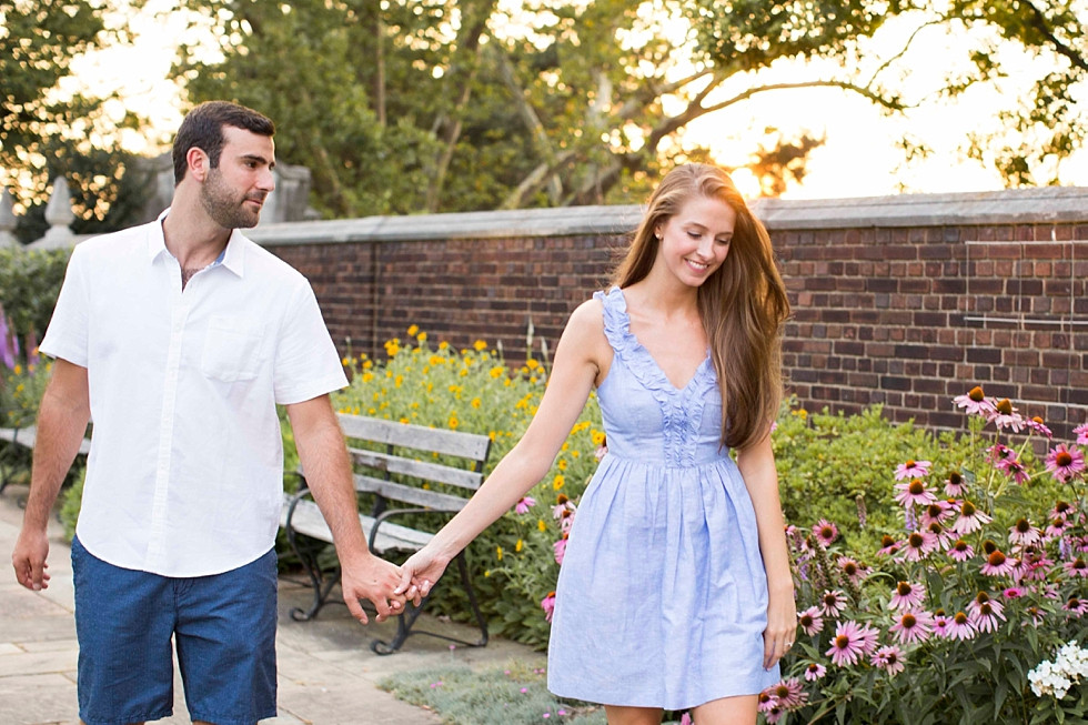 couple walking holding hands completely in love; man gazing at fiancee adoringly