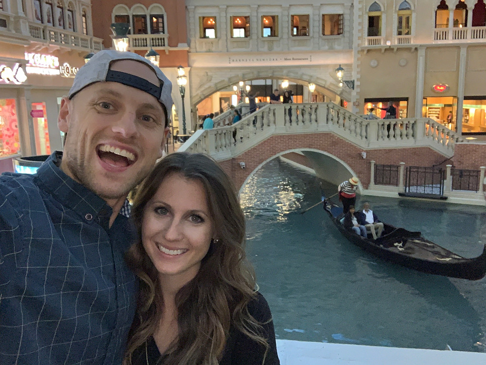 young couple at The Venetian Hotel in Las Vegas with gondola in the background