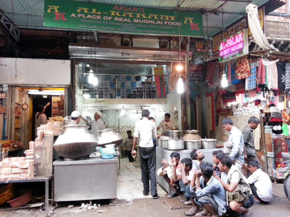 Hungry men waiting for their food outside Al-Karam