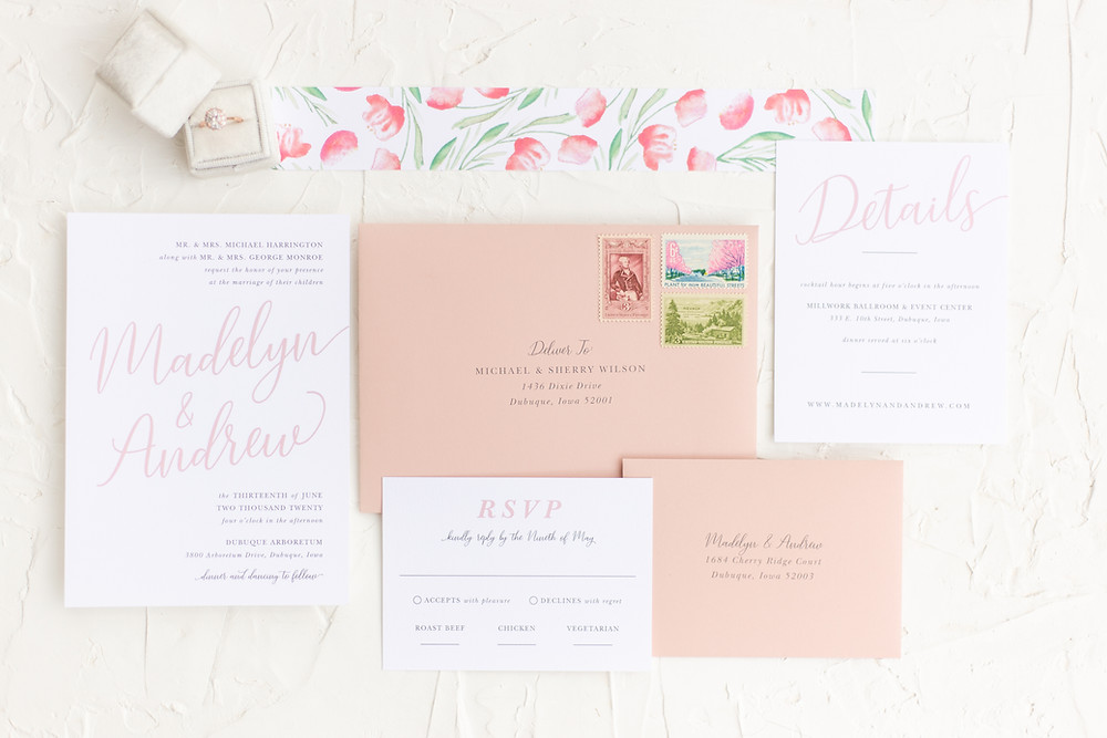 Flat Lay of Blush Pink Text Based Semi Custom Wedding Invitation Suite with Floral Accents