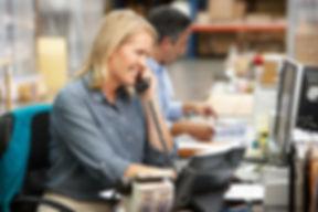 Businesswoman Working At Desk In Warehou
