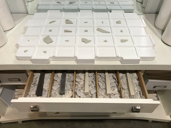 """Grid with Porcelain sherds, 2017, with Cabinet with a Partial Archive of Porcelain Slag, Chipped Obelisks, 7"""", the Sanded 7"""" Model for the Original Plaster Cast, and The Complete Collection of Three Glaze Tests, 2018."""