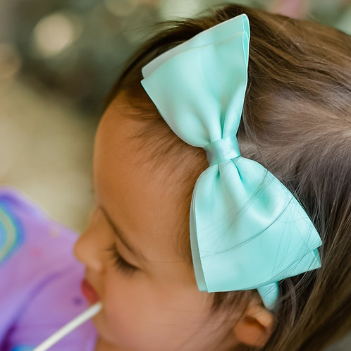aqua blue bow in a toddler's hair