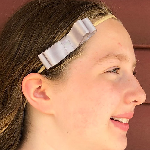 small silver bow in a girls hair
