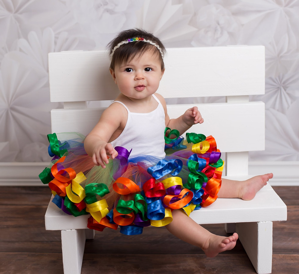 Baby girl in a rainbow ribbon tutu skirt.