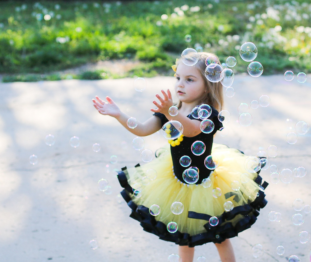 little girl in a tutu playing with bubbles