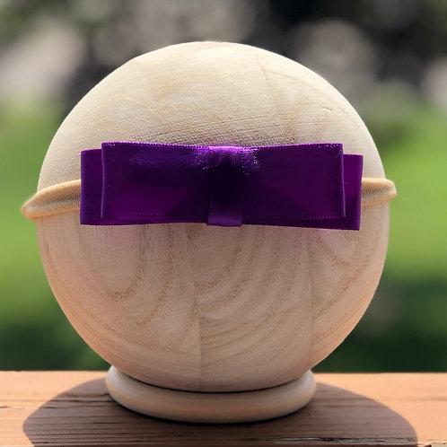 purple hair bow on newborn head