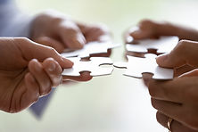 Close up hands of four businesspeople hold pieces of white puzzle, assemble jigsaw, put it