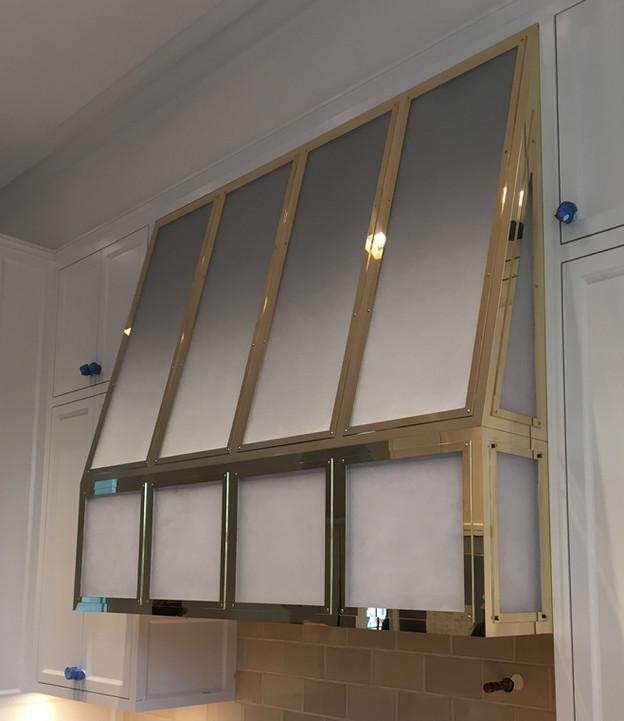 Custom polished brass rangehood during installation