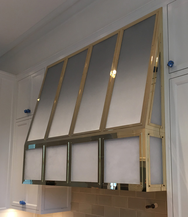 Custom polished brass rangehood during installation