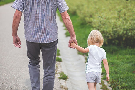 man-and-child-walking-near-bushes-during