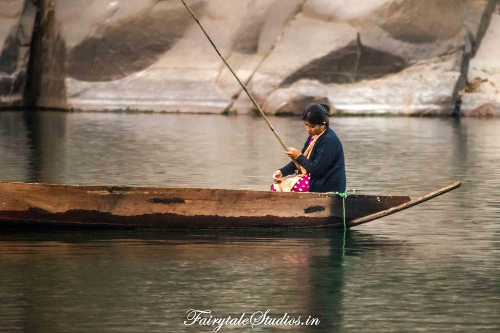 A lady looks sadly in the water hoping to catch fishes