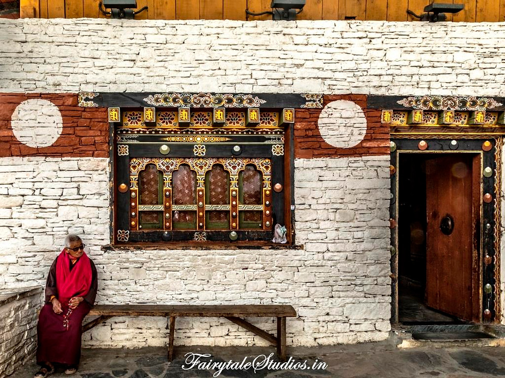 Elderly reciting prayers at a Buddhist temple in Bhutan