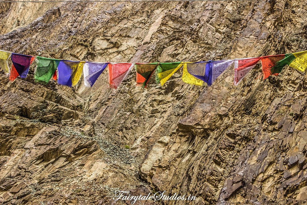 Tibetan prayer flags against resolute and tough rocky mountains (The Zanskar Odyssey travelogue)
