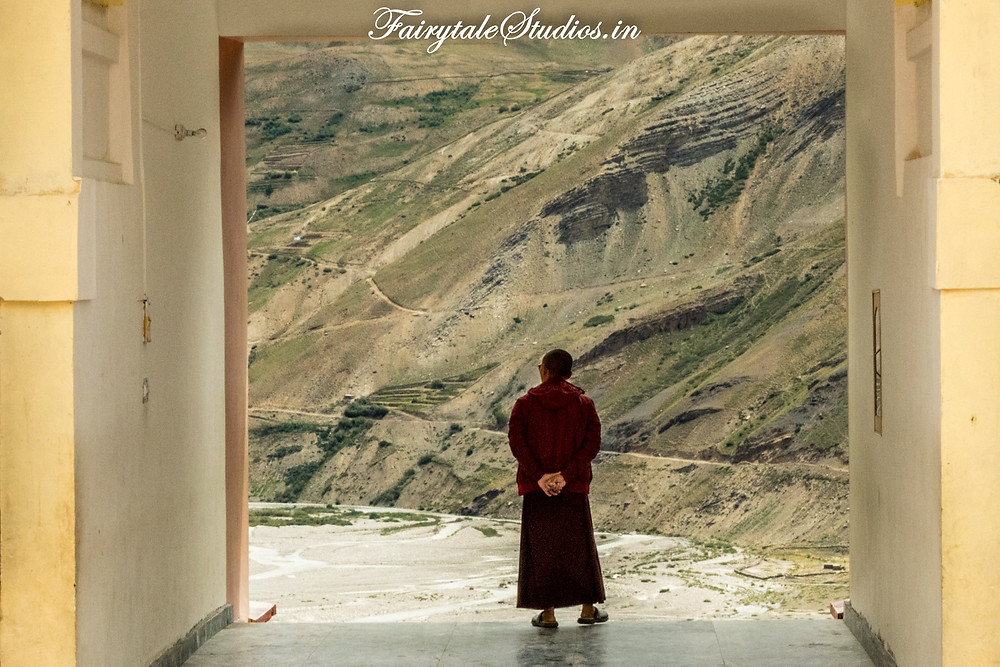Monk in the Kungri monastery staring at the beautiful landscape outside - Pin Valley - Spiti Valley, Himachal Pradesh, India