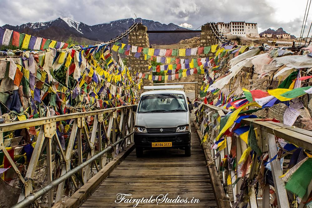 Wooden bridge with Tibetan prayer flags with Stakna Monastery in the background (The Zanskar Odyssey)