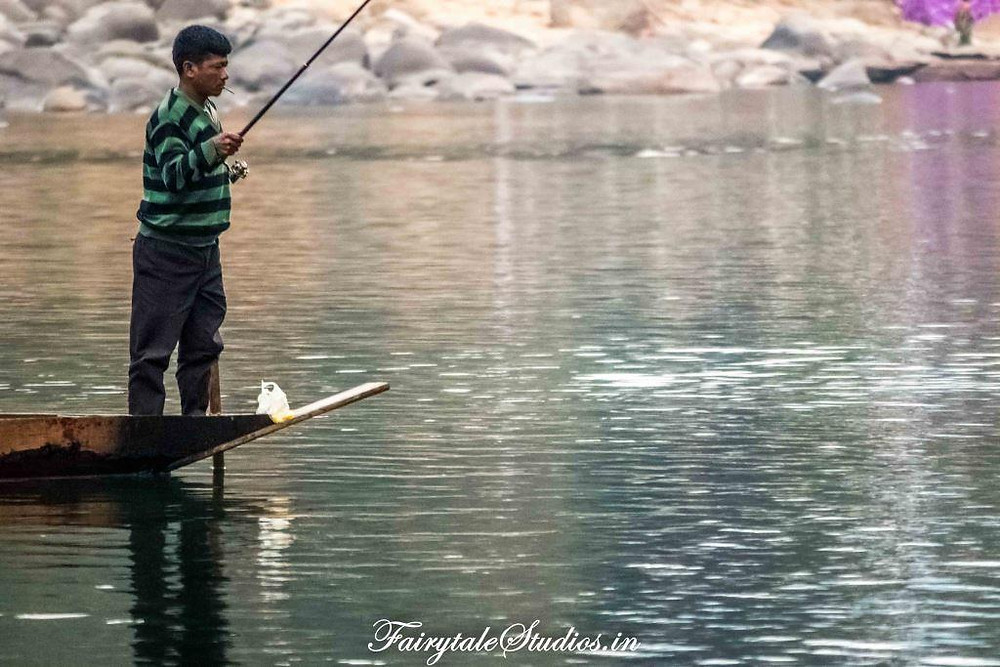 A fisherman fishing from his boat while having locally made cigarette