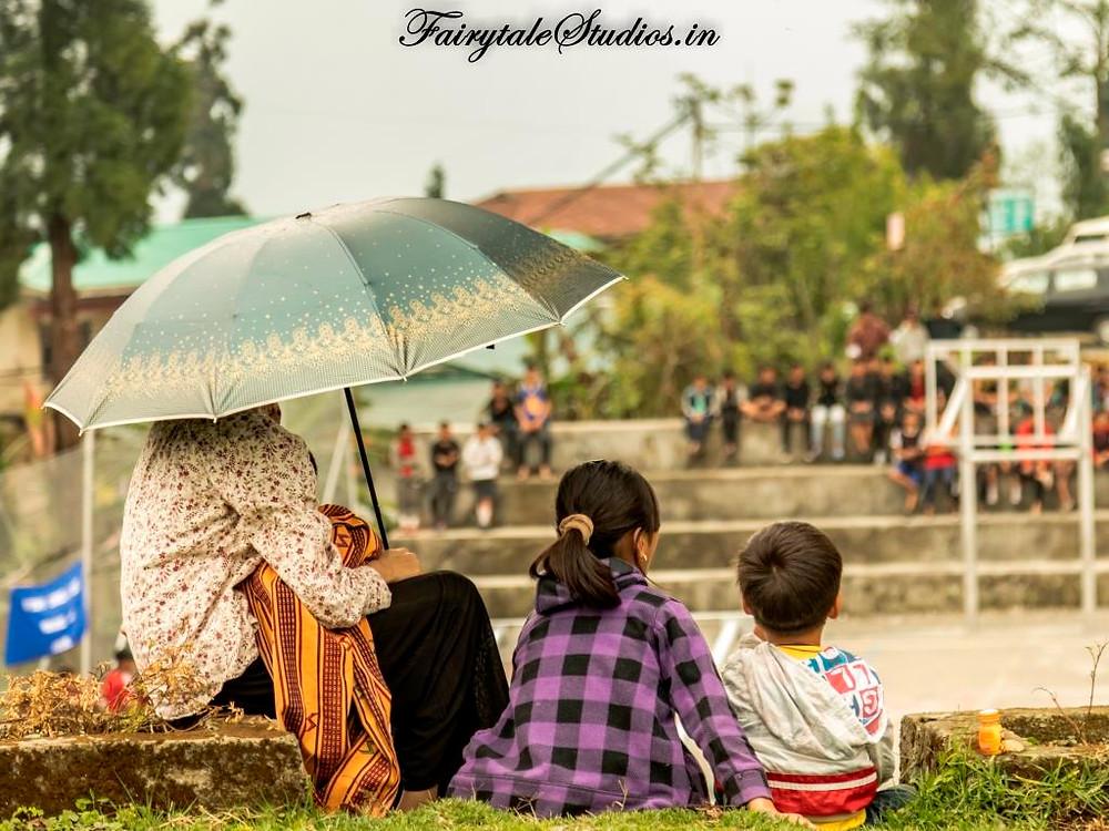 Women watching a volleyball match in Bhutan with her children - The Bhutan Odyssey