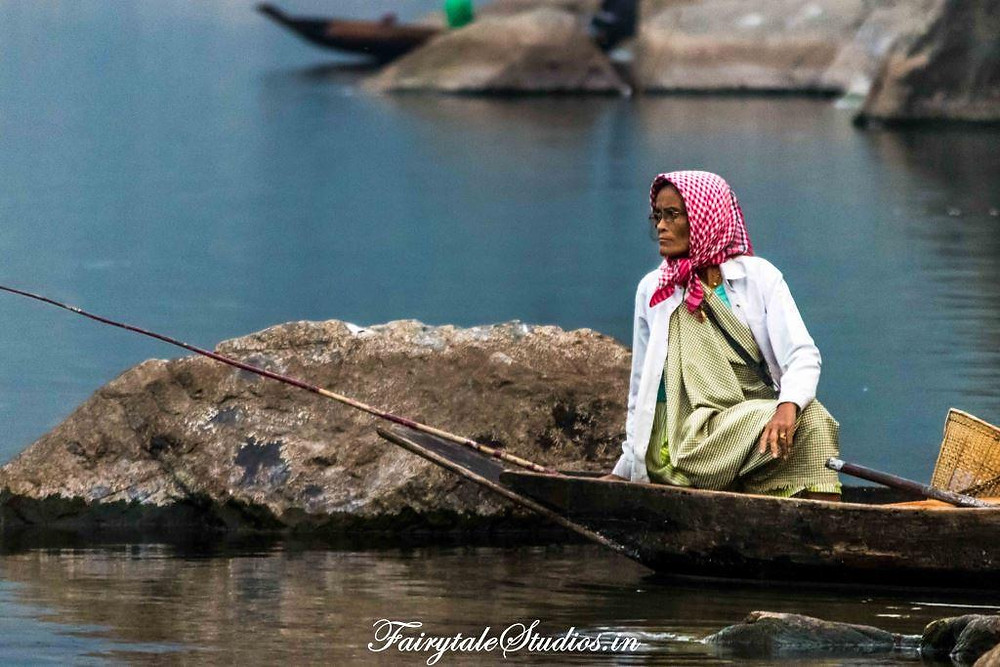 An old woman sitting on her boat looking for fishes in Umngot river