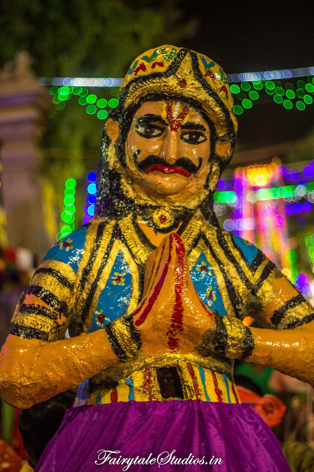 A costumed mascot at the front of the Dussehra carnival greeting people with Namaste.