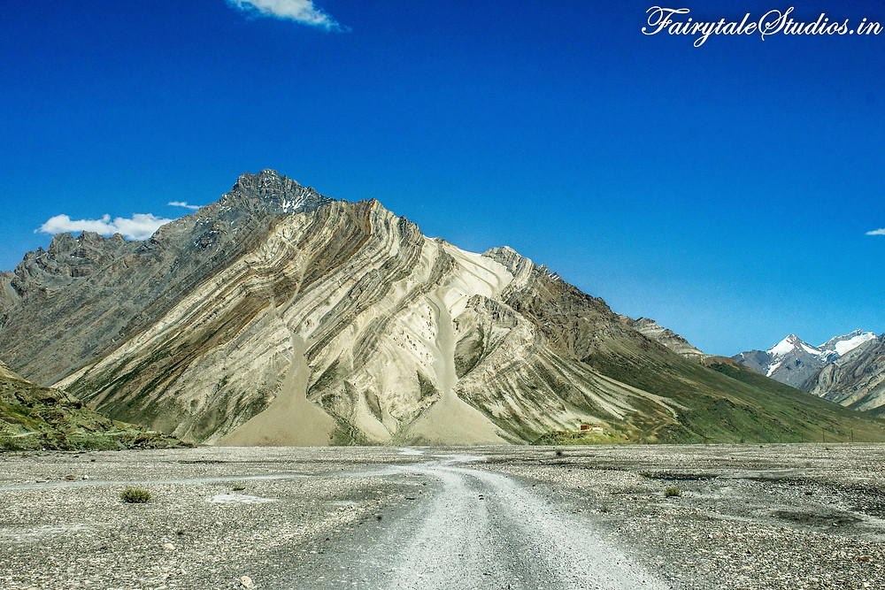 A trail created by vehicles going towards the textured mountains. One can spot a small hill on the right which houses the Rangdum monastery (The Zanskar Odyssey Travelogue)