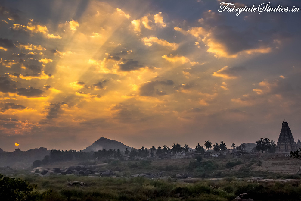 As the sun rises in Hampi with Virupaksha temple and Mathanga hill in sight