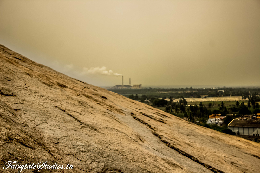 A distant industry producing smoke seen from steps on the way to Bhongir fort