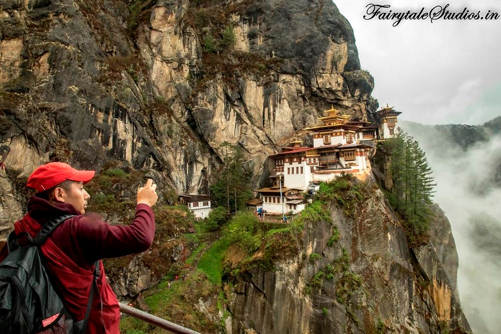 A monk clicking the Taktsang monastery in Paro, Bhutan