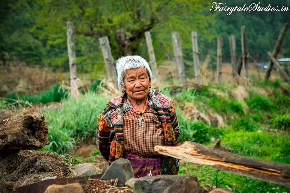 An old woman working in a field in Phobjikha Valley, Bhutan