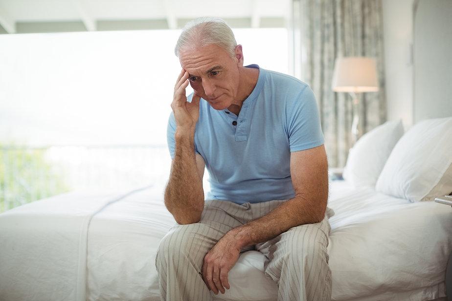 stressed-senior-man-sitting-on-bed-B52U3