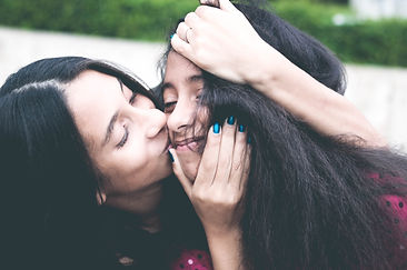 Mother hugging teenager daughter.