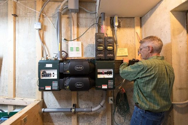 Dr. Steyn checks the solar and wind charge controllers and the inverters of his off-grid system.