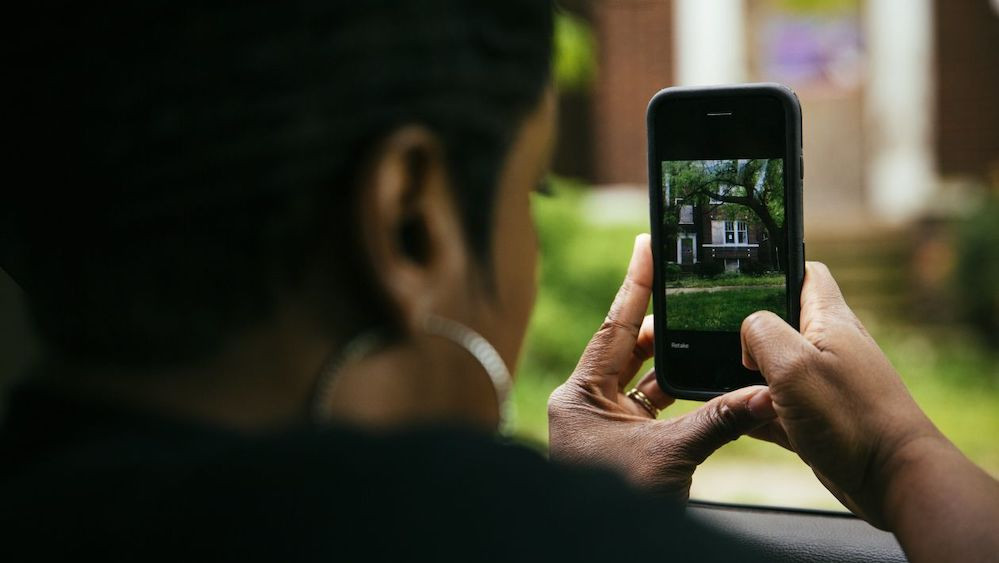 Tyra Johnson-Morris takes a photo of a property in Chicago using DealMachine, a real-estate investment app that uses GPS to identify property owners.