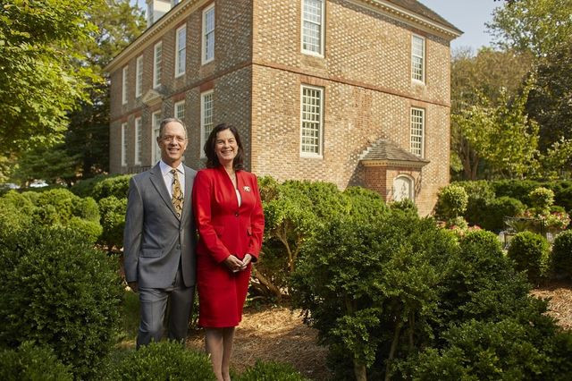 College of William & Mary President Katherine A. Rowe and her husband, Bruce Jacobson, stand in the gardens in front of the President's House, a three-story Colonial Georgian mansion built in 1732.