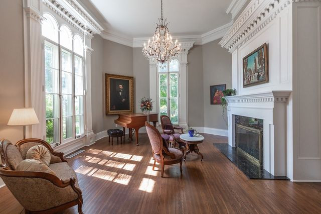 The music room is one of the favorite places in the home for Cornell President Jonathan Brand and his wife Rachelle LaBarge. The portrait on the left is of former Cornell president William F. King, painted by Louis O. Jurgensen. Mr. King donated the house to the college when he retired as president, on the condition that he could continue to live in it until he died. Ms. LaBarge hung a portrait of a flamenco dancer across from Mr. King's portrait to 'remind him to lighten up,' says Mr. Brand.