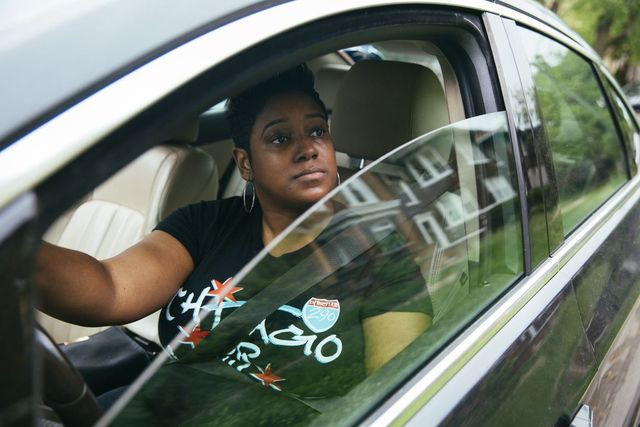Ride-share driver Tyra Johnson-Morris scouts in her car in Chicago.