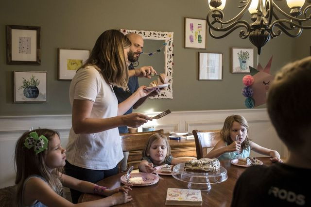 Lindsay Mahaffey, standing left, and her husband, Terry, serve cake and ice cream for their three daughters at a family birthday party in their home in Apex, N.C.