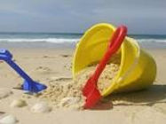 bucket and spade on beach near caravans for hire at Butlins in Skegness