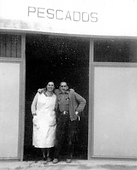 o	A man and a women under a sign where it's written down Pescados