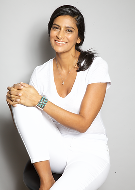 Lubna white jeans seated smile to camera