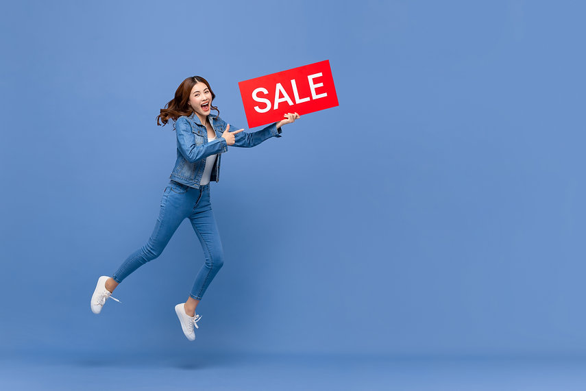 Excited Asian woman in casual jean clothes jumping with red sale sign in hand isolated on