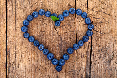 Shape of heart made of blueberries on wo