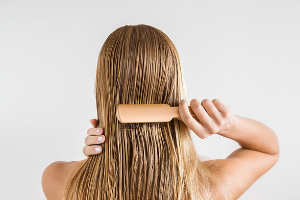 Woman with comb brushing her wet blonde