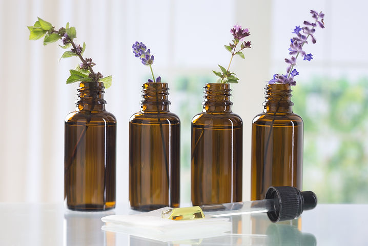 brown bottle  with aromatic herbs for es